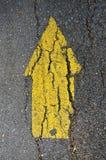 Colore giallo della freccia sulla via Immagine Stock