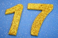 Colore giallo di numero diciassette sopra un fondo blu Anniversar Immagine Stock