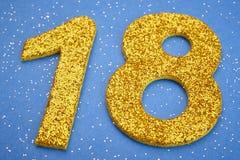 Colore giallo di numero diciotto sopra un fondo blu anniversario Immagini Stock Libere da Diritti