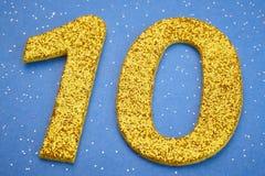 Colore giallo di numero dieci sopra un fondo blu anniversario Immagine Stock