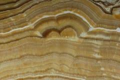 Colore giallo-marrone dell'onyx naturale della pietra con un bello modello fotografia stock