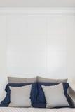 Colore grigio e blu dei cuscini sul letto con il picchiettio bianco di progettazione della parete fotografie stock libere da diritti