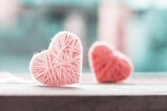 colore morbido che tricotta lana nella forma di cuore su spirito di legno d'annata fotografia stock