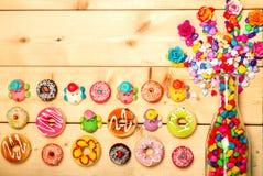 Colore pastello delle guarnizioni di gomma piuma dolci con il fiore rosa su fondo di legno Immagine Stock