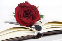 Colore rosso del ith del giornale w di rosa e penna Fotografie Stock