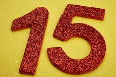 Colore rosso di numero quindici sopra un fondo giallo anniversario Immagini Stock