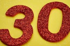 Colore rosso di numero trenta sopra un fondo giallo anniversario Fotografia Stock Libera da Diritti