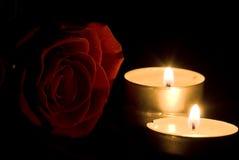 Colore rosso di rosa e candele nella nerezza immagini stock