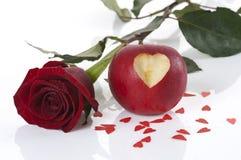 Colore rosso di rosa e mela con cuore intagliato Fotografia Stock
