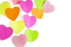 Colorea corazones de los papeles de nota en la pared blanca Fotos de archivo libres de regalías