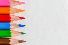Coloreado cerca encima de los lápices en el fondo blanco Fotografía de archivo