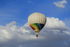 colored aerostatic balloon flying in a blue sky with white clouds stock photo