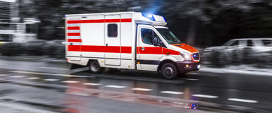Colored ambulance car speeding in black and white. A colored ambulance car speeding in black and white stock photography