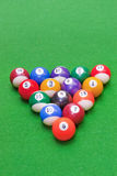 Colored american pool balls. Set of colored pool balls in triangle on green baize, top view with selective focus stock photo