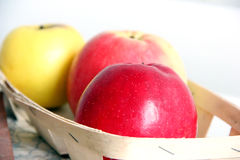 Colored apples in a basket Stock Photos