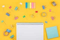 Colored art hobby set. Multicolored office supplies and blank notepad  laying on yellow background top view. Creative set for hobby Royalty Free Stock Image