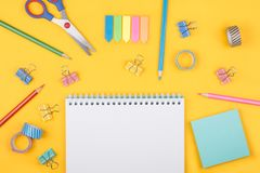 Colored art hobby set. Multicolored set of pencils and blank notepad and office supplies  laying on yellow background top view. Creative set for hobby Royalty Free Stock Images