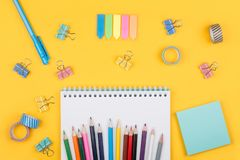 Colored art hobby set. Multicolored set of pencils and blank notepad and office supplies  laying on yellow background top view. Creative set for hobby Stock Photo