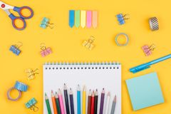 Colored art hobby set. Multicolored set of pencils and blank notepad and office supplies  laying on yellow background top view. Creative set for hobby Stock Photos
