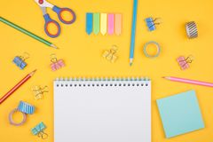 Colored art hobby set. Multicolored set of pencils and blank notepad and office supplies  laying on yellow background top view. Creative set for hobby Stock Photography