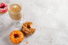 Colored assorted donuts with glaze and cup of coffee stock image