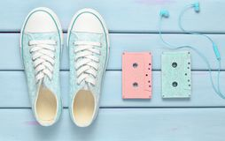 Colored audio cassettes, headphones, sneakers shoes on a purple pastel background. Old-fashioned technologies. Top view. Flat lay.  stock images