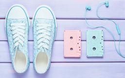 Colored audio cassettes, headphones, sneakers shoes on a purple pastel background. Old-fashioned technologies. Top view. Flat lay. Colored audio cassettes stock image