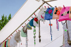 Colored baby caps hang on rope village fair Royalty Free Stock Images