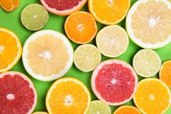 Colored background of different citrus round lobules. On a green table stock photos
