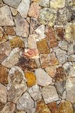 Colored background for the facade of the house in light yellow and pink shades of raw natural stone. Mottled multi colored background for the facade of the house stock photo