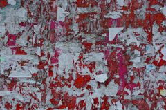 Colored texture of torn paper ads on a red board. Colored background of torn paper ads on a red board royalty free stock image