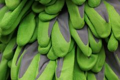 Gray green fabric texture of working gloves in a heap. Colored background of working gloves in a pile stock image