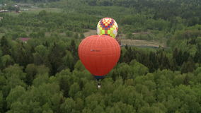 Colored balloons flying over forest and cottages stock video