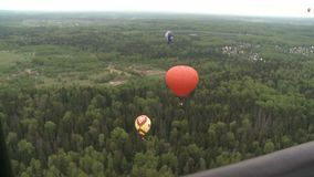 Colored balloons flying over forest and cottages. Two colored balloons flying low over the green tree tops during on a clear day aerial view stock video footage