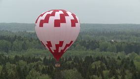 Colored balloons flying over forest and cottages. Two colored balloons flying low over the green tree tops during on a clear day aerial view stock footage