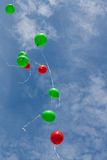 Colored balloons on sky. Red and green balloons in the sky Royalty Free Stock Photos