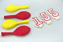 Colored balloons and some candles in the shape of numbers. Balloons of yellow and red colors with some candles forming the number 155, flag, catalonia, catalan royalty free stock images