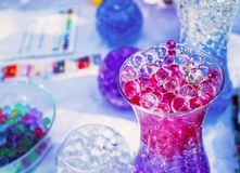 Colored balls of absorbent hydrogel in a glass vase royalty free stock images