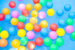 Colored balls floating in kiddie pool Stock Images