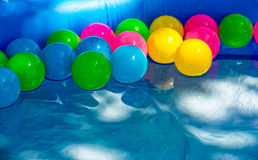 Colored balls swim in a small pool Royalty Free Stock Photography