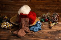 Colored balls of thread, multi-colored knitted socks and Christmas tree decorations on wooden background stock image