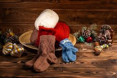 Colored balls of thread, multi-colored knitted socks and Christmas tree decorations on wooden background stock photography