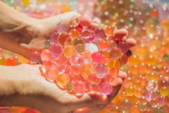 Colored balls of water beads, hydrogel in in hands. Sensory expe Royalty Free Stock Images