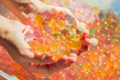 Colored balls of water beads, hydrogel in in hands. Sensory expe. Riences Stock Photography