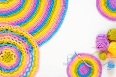 Color striped crocheted crochets. White background. Colored balls of yarn. View from above. Rainbow colors. All colors. Yarn for knitting. Skeins of yarn Stock Images