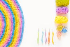 Color striped crocheted crochets. White background. Colored balls of yarn. View from above. Rainbow colors. All colors. Yarn for knitting. Skeins of yarn Stock Photo