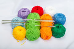 Colored balls of yarn, wool on white fabric. Royalty Free Stock Image