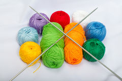 Colored balls of yarn, wool on white fabric. Stock Images