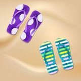 Colored beach slippers the sandy background Royalty Free Stock Photography