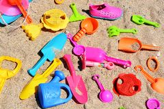 Colored beach toys in sand background, kids have fun at the seaside. Beach toys in sand background, kids have fun at the seaside Stock Photo